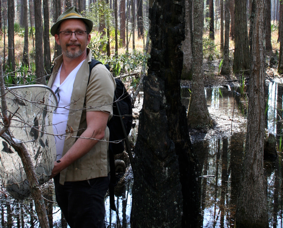 picture of Mark Mandica with a net in a swamp like area